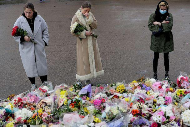 PHOTO: People look at the floral tributes at the bandstand on Clapham Common, London, Monday March 15, 2021. On Saturday hundreds of people disregarded a judge's ruling and police requests by gathering at Clapham Common in honor of Sarah Everard. (Kirsty Wigglesworth/AP)