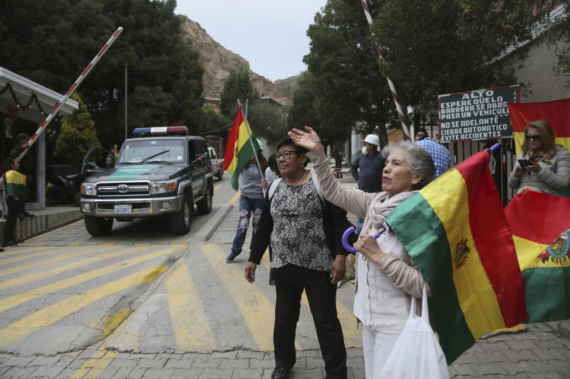 People protest at the entrance leading to the residence of Mexico's ambassador to help make sure nine former officials from the government of deposed Bolivian President Evo Morales, who have taken refuge inside, do not leave the country, amid police presence in La Paz, Bolivia, Monday, Dec. 30, 2019. Bolivia's interim government is expelling the top Mexican and Spanish diplomats in the country over an alleged attempt by members of Bolivia's former government to leave refuge in the Mexican embassy with Spanish help and flee the country. (AP Photo/Luis Gandarillas)