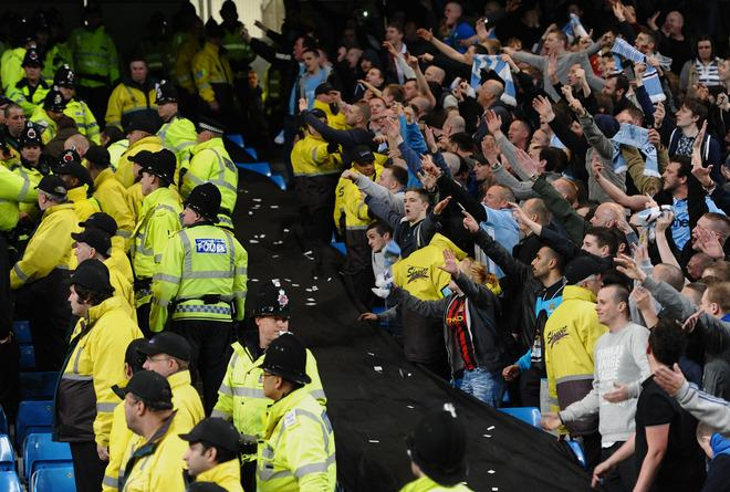 """Manchester City fans (R) gesture towards Manchester United fans after their team won 1-0 during their English Premier League football match at The Etihad stadium in Manchester, north-west England on April 30, 2012. AFP PHOTO/PAUL ELLIS  RESTRICTED TO EDITORIAL USE. No use with unauthorized audio, video, data, fixture lists, club/league logos or """"live"""" services. Online in-match use limited to 45 images, no video emulation. No use in betting, games or single club/league/player publications.PAUL ELLIS/AFP/GettyImages"""