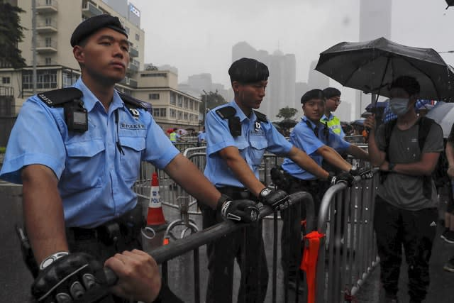 Policemen stand guard in the rain as protesters gather near the Legislative Council in Hong Kong