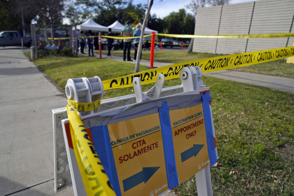 A sign points to a line at a COVID-19 vaccination site for health care workers at Ritchie Valens Recreation Center Wednesday, Jan. 13, 2021, in Pacoima, Calif. (AP Photo/Marcio Jose Sanchez)
