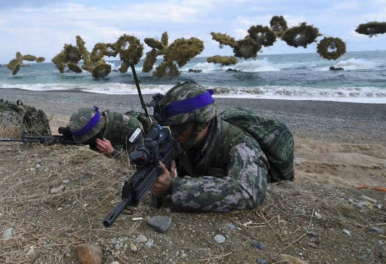 South Korean Marines take position on a beach as amphibious assault vehicles fire smoke shells during a joint landing operation by US and South Korean Marines in the southeastern port of Pohang on April 2, 2017