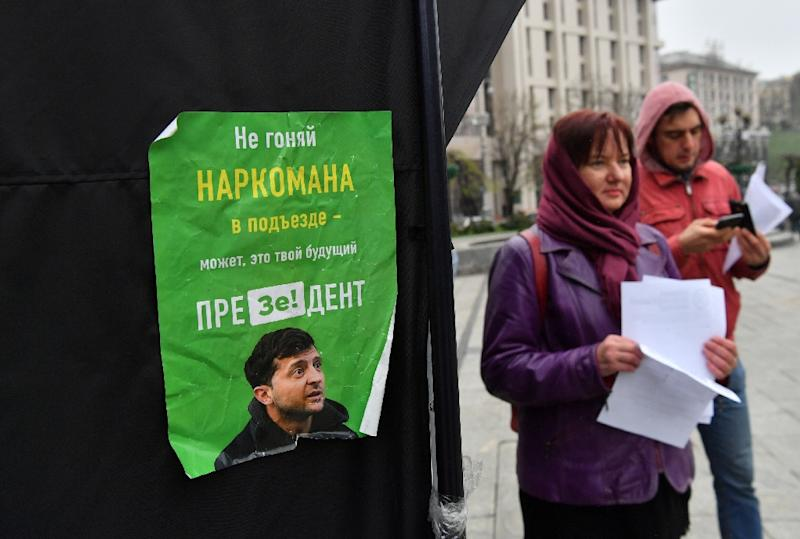 Party suporters hand out leaflets to passersby outside of the incumbent President Petro Poroshenko's campaigning tent, decorated with signs that read 'Stop' or 'Ze', a pun on the name of rival candidate comedian Volodymyr Zelensky