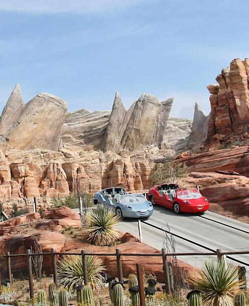 """In this 2012 image released by Disney theme parks, Radiator Springs Racers are shown at Cars Land, a new attraction based on the Disney-Pixar animated series """"Cars,"""" at Disney California Adventure park in Anaheim, Calif. Cars Land features three family attractions showcasing characters and settings from the film. (AP Photo/Disney, Paul Hiffmeyer)"""