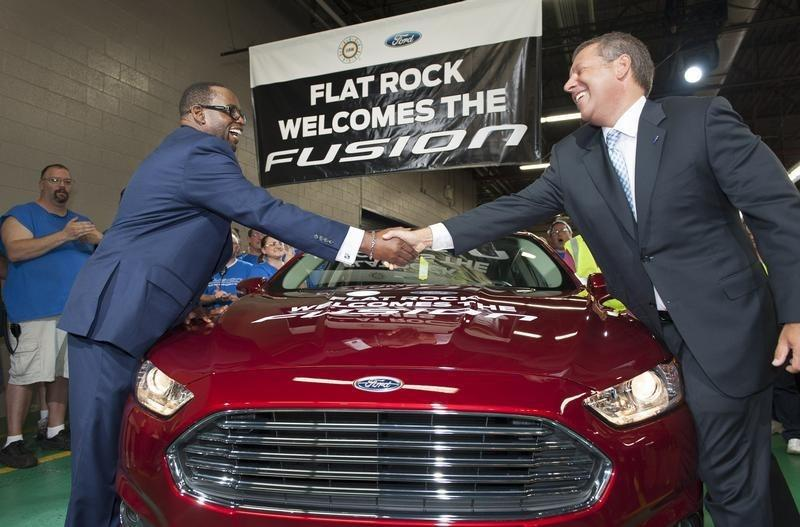 Joe Hinrichs, Ford's president of the Americas (R) and Jimmy Settles, UAW vice president of the National Ford Department, shake hands over the first 2014 Fusion produced in the United States in Flat Rock