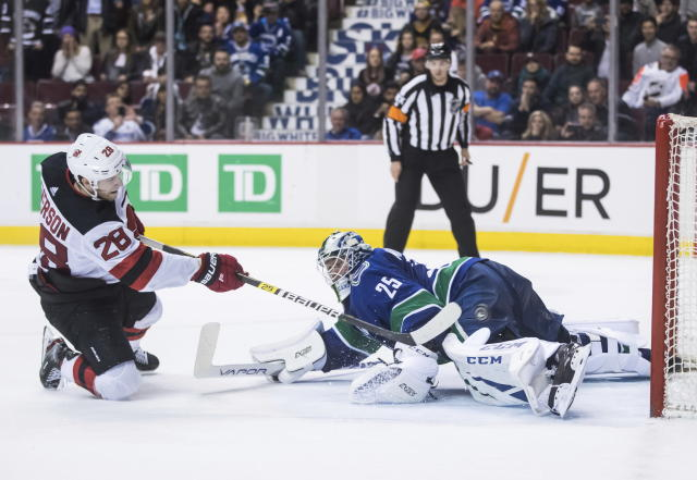 New Jersey Devils' Damon Severson, left, scores against Vancouver Canucks goalie Jacob Markstrom, of Sweden, in the shootout of an NHL hockey game Friday, March 15, 2019, in Vancouver, British Columbia. (Darryl Dyck/The Canadian Press via AP)