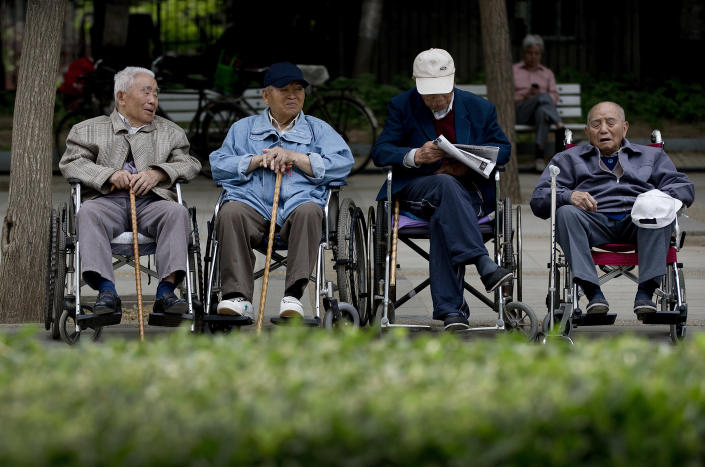 In this Thursday, May 23, 2013 photo, a group of elderly men take a rest on their wheelchairs at a park in Beijing. New wording in the law requiring people to visit or keep in touch with their elderly parents or risk being sued came into force Monday, July 1, 2013, as China faces increasing difficulty in caring for its aging population. (AP Photo/Andy Wong)