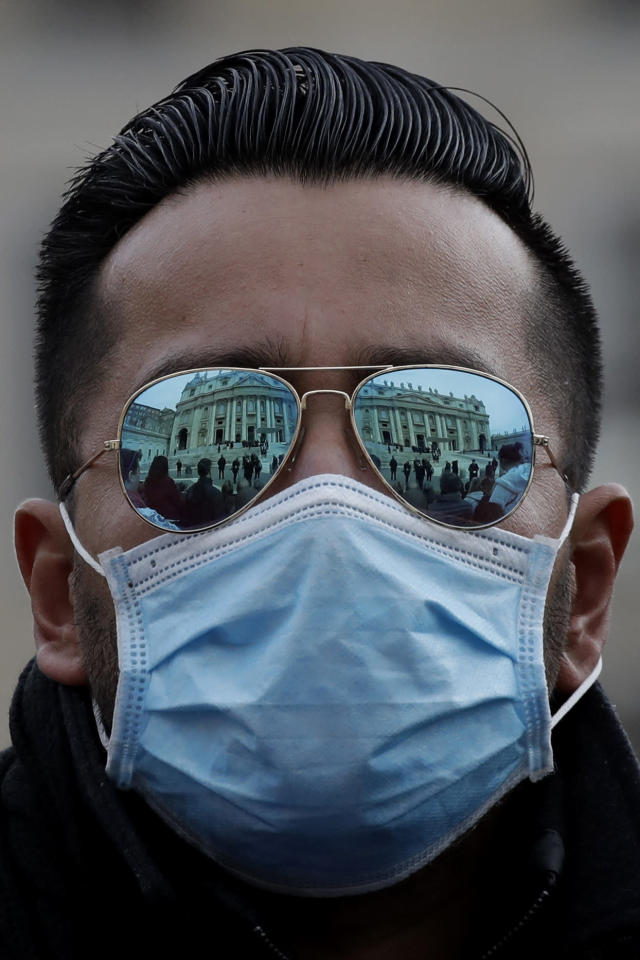 A man wears a face mask in St. Peter's Square at the Vatican during Pope Francis' weekly general audience, Wednesday, Feb. 26, 2020. The viral outbreak that began in China and has infected more than 80,000 people globally, so far caused 323 cases and 11 deaths in Italy. (AP Photo/Alessandra Tarantino)