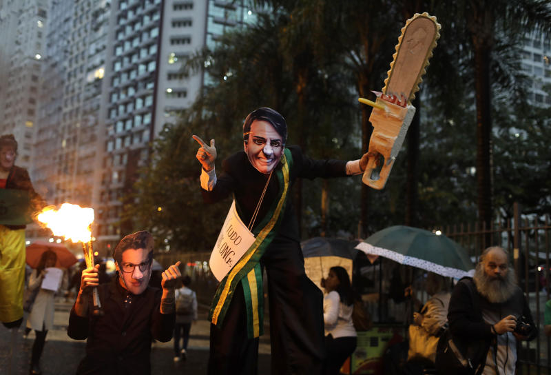 A demonstrator wearing a Brazilian President Jair Bolsonaro mask and brandishing a fake chainsaw, center, with another wearing a mask o Brazil's Environment Minister Ricardo Salles, march in defense of the Amazon in Rio de Janeiro, Brazil, Thursday, Sept. 5, 2019. Bolsonaro will not attend a reunion of regional leaders whose countries include parts of the Amazon rainforest that is scheduled for Friday in Colombia, with government spokesman Otavio Rego Barros saying the president could not go because of upcoming surgery to treat a hernia. Bolsonaro was stabbed in the abdomen during the presidential campaign. (AP Photo/Silvia Izquierdo)