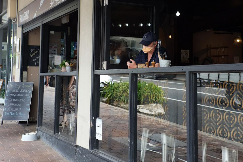 A customer wearing a protective mask sits in a cafe during lunch time in the Crows Nest suburb of Sydney.