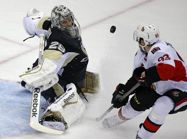 Pittsburgh Penguins goalie Marc-Andre Fleury (29) makes a save on a shot by Ottawa Senators' Mika Zibanejad (93) in the first period of an NHL hockey game in Pittsburgh, Monday, Feb. 3, 2014. (AP Photo/Gene J. Puskar)