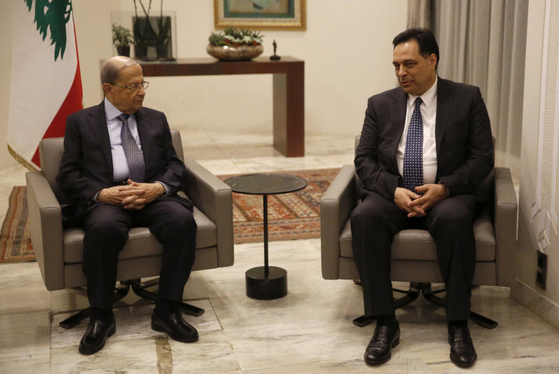Lebanese President Michel Aoun, left, meets with Lebanese newly-assigned Prime Minister, Hassan Diab, right, at the presidential palace, in Baabda, east of Beirut, Lebanon, Thursday, Dec. 19, 2019.   Aoun named Diab as prime minister after a day of consultations with lawmakers in which he gained a simple majority of the 128-member parliament. Sixty-nine lawmakers, including the parliamentary bloc of the Shiite Hezbollah and Amal movements as well as lawmakers affiliated with President Michel Aoun gave him their votes. (AP Photo/Hussein Malla)