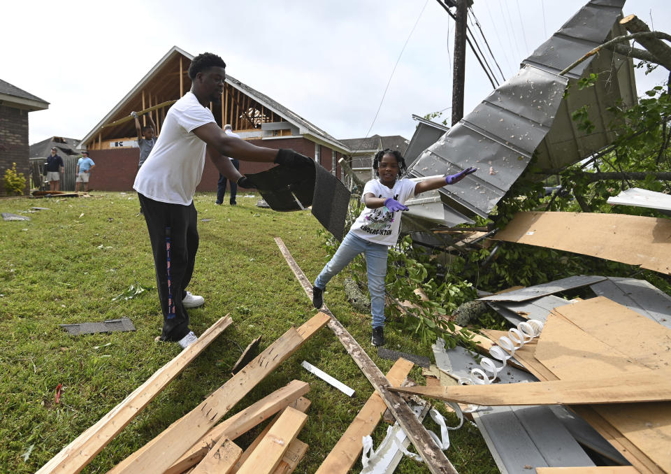 Derrick Pounds and his daughter, Madison, 6, clean up debris around their residence on Elvis Presley Drive in Tupelo, Miss., Monday, May 3, 2021. Multiple tornadoes were reported across the state on Sunday. (AP Photo/Thomas Graning)