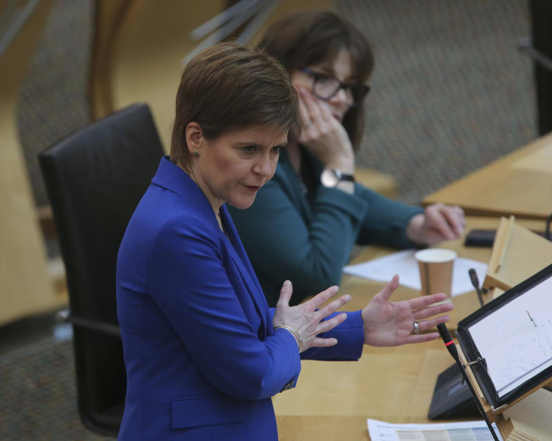 "Scotland's First Minister Nicola Sturgeon gestures, during the First Minister's Statement on Covid-19 at the Scottish Parliament, in Holyrood, Edinburgh, Scotland, Thursday May 21, 2020. Sturgeon presented a ""map"" for easing coronavirus restrictions in the months ahead while observing social distancing guidelines. (Fraser Bremner/Scottish Daily Mail/PA via AP)"