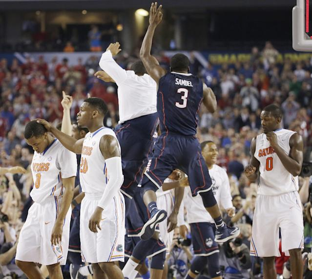 Connecticut players including Terrence Samuel (3) celebrate after beating Florida 63-53 during their NCAA Final Four tournament college basketball semifinal game Saturday, April 5, 2014, in Arlington, Texas. (AP Photo/David J. Phillip)