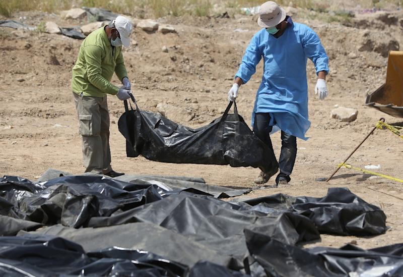 Iraqi security forces work at the site of a mass grave containing the remains of people believed to have been slain by jihadists of the Islamic State (IS) group at the Speicher camp in the city of Tikrit, on April 12, 2015