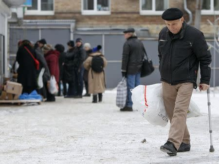 An internally displaced person from eastern Ukraine walks with bags outside a volunteer centre in Kiev