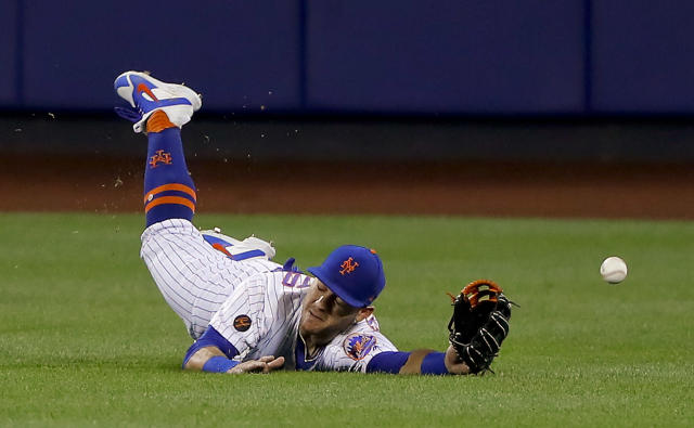 New York Mets center fielder Michael Conforto dives for but can't make the play on a ball hit by Los Angeles Dodgers' Yasiel Puig during the eighth inning of a baseball game Saturday, June 23, 2018, in New York. (AP Photo/Julie Jacobson)