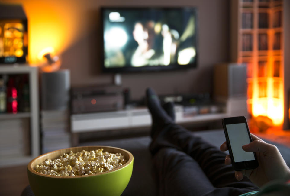 Man relaxing at home watching tv and eating popcorn and surfing internet