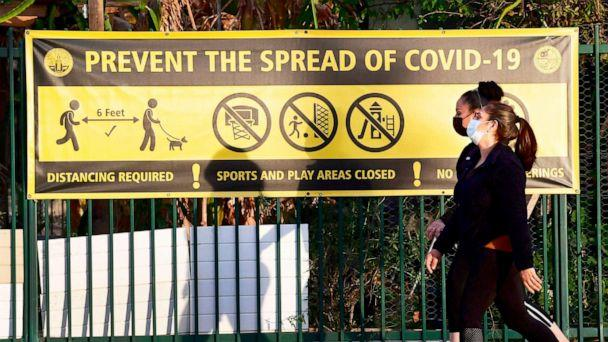 PHOTO: Pedestrians wearing facemasks walk past a prevent the spread of Covid-19 banner in Los Angeles, Jan. 19, 2020. (Frederic J. Brown/AFP via Getty Images)