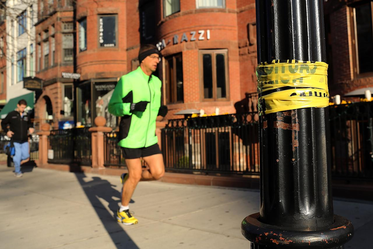BOSTON, MA - APRIL 16:  A man jogs down a street near the scene of a twin bombing at the Boston Marathon on April 16, 2013 in Boston, Massachusetts. The twin bombings, which occurred near the marathon finish line, resulted in the deaths of three people while hospitalizing at least 128. The bombings at the 116-year-old Boston race, resulted in heightened security across the nation with cancellations of many professional sporting events as authorities search for a motive to the violence.  (Photo by Spencer Platt/Getty Images)