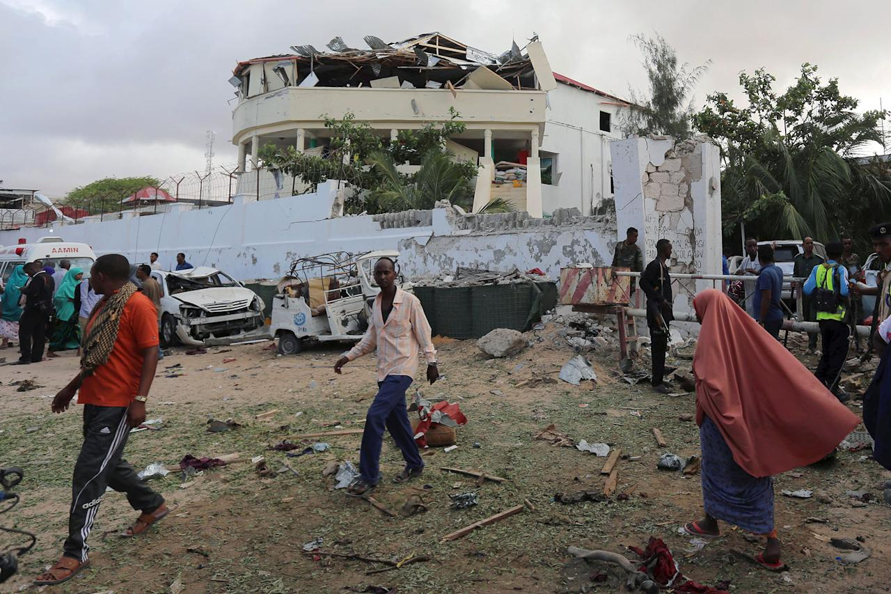 <p>People stand outside the scene of an attack on a hotel and an adjacent restaurant in Mogadishu, Somalia June 15, 2017. (Photo: Stringer/Reuters) </p>
