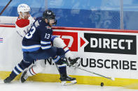 Winnipeg Jets' Pierre-Luc Dubois (13) and Montreal Canadiens' Nick Suzuki (14) compete for the puck during the first period of an NHL hockey game Saturday, Feb. 27, 2021, in Winnipeg, Manitoba. (John Woods/The Canadian Press via AP)