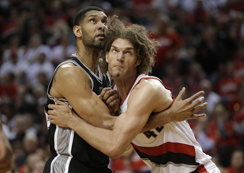 Portland Trail Blazers' Robin Lopez, right, and San Antonio Spurs' Tim Duncan, left, battle under the boards in the second half during Game 3 of a Western Conference semifinal NBA basketball playoff series Saturday, May 10, 2014, in Portland, Ore. The Spurs won 118-103. (AP Photo/Rick Bowmer)