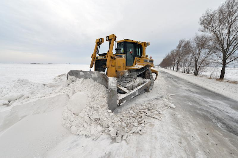 A road sweeping vehicle clears snow from the road near the city of Vrbas, northern Serbia, Saturday, Feb. 1, 2014. Snow drifts formed by stormy winds have blocked two passenger trains and dozens of vehicles in northern Serbia, while authorities closed down several roads and a border crossing with Hungary. The state railway company says two trains to and from Hungary got stuck early on Saturday because of meters-high snow piles that formed on the railway. Emergency officials say several dozen passengers from the trains will be evacuated. (AP Photo/Darko Dozet) SERBIA OUT