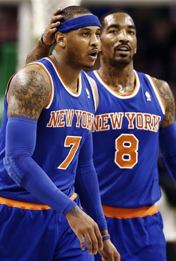 New York Knicks' J.R. Smith (8) pats the head of Carmelo Anthony after a timeout was called by the Boston Celtics during the second quarter of an NBA basketball game in Boston, Tuesday, March 26, 2013. (AP Photo/Winslow Townson)