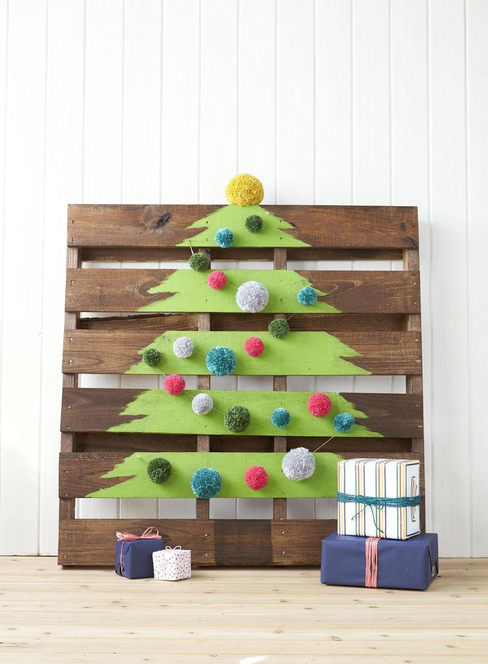 """<p>Paint a tree on a shipping crate (you can find 'em for cheap on eBay), and embellish the slats with pom-poms.</p><p><a class=""""link rapid-noclick-resp"""" href=""""https://go.redirectingat.com?id=74968X1596630&url=https%3A%2F%2Fwww.ebay.com%2Fsch%2Fi.html%3F_from%3DR40%26_trksid%3Dp2053587.m570.l1313.TR10.TRC0.A0.H0.Xshipping%2Bpallet.TRS0%26_nkw%3Dshipping%2Bpallet%26_sacat%3D0&sref=https%3A%2F%2Fwww.countryliving.com%2Fhome-design%2Fdecorating-ideas%2Fadvice%2Fg1247%2Fholiday-decorating-1208%2F"""" rel=""""nofollow noopener"""" target=""""_blank"""" data-ylk=""""slk:SHOP PALLETS"""">SHOP PALLETS</a></p>"""
