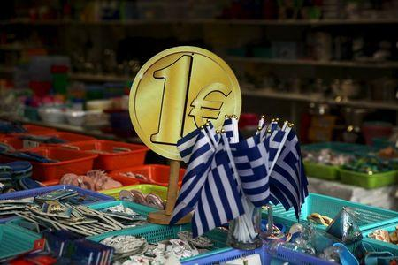 Greek flags are displayed for sale for one Euro at a shop in central in Athens, Greece July 26, 2015. Greek banks are set to keep broad cash controls in place for months, until fresh money arrives from Europe and with it a sweeping restructuring, officials believe. REUTERS/Yiannis Kourtoglou