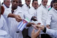 Cuban doctors receive Cuban and Italian flags during a farewell ceremony before departing to Italy to assist, amid concerns about the spread of the coronavirus disease outbreak, in Havana