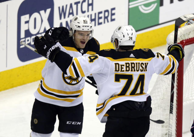Boston Bruins forward Karson Kuhlman, left, celebrates his goal against the Columbus Blue Jackets with teammate forward Jake DeBrusk during the third period of an NHL hockey game in Columbus, Ohio, Tuesday, April 2, 2019. The Bruins won 6-2. (AP Photo/Paul Vernon)