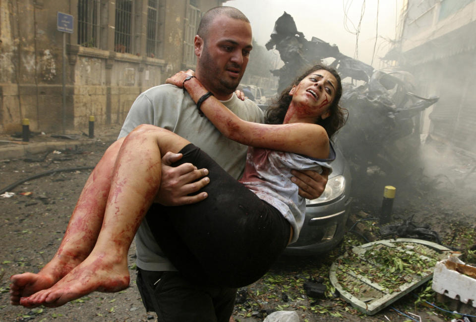 A wounded woman is carried at the site of an explosion in Ashrafieh, central Beirut, October 19, 2012. At least two people were killed and 15 wounded by a huge bomb that exploded in a street in central Beirut on Friday, witnesses and a security source said. REUTERS/Hasan Shaaban (LEBANON -Tags: CIVIL UNREST)
