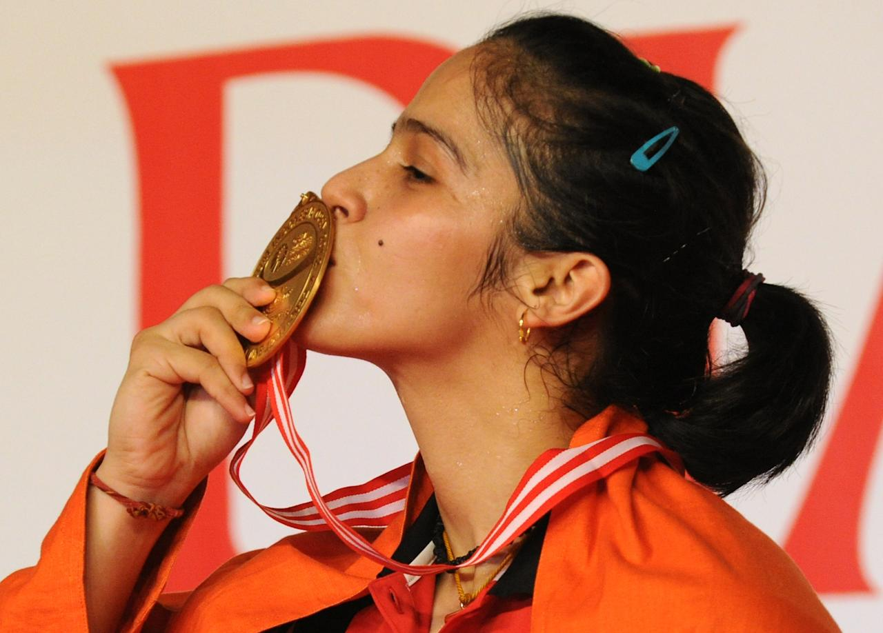 Saina Nehwal of India kisseS her gold medal after winning the badminton final against Li Xuerui of China at the Indonesian Open Superseries in Jakarta on June 17, 2012.  Nehwal defeated Li 13-21, 22-20, 21-19. AFP PHOTO / ROMEO GACAD        (Photo credit should read ROMEO GACAD/AFP/GettyImages)