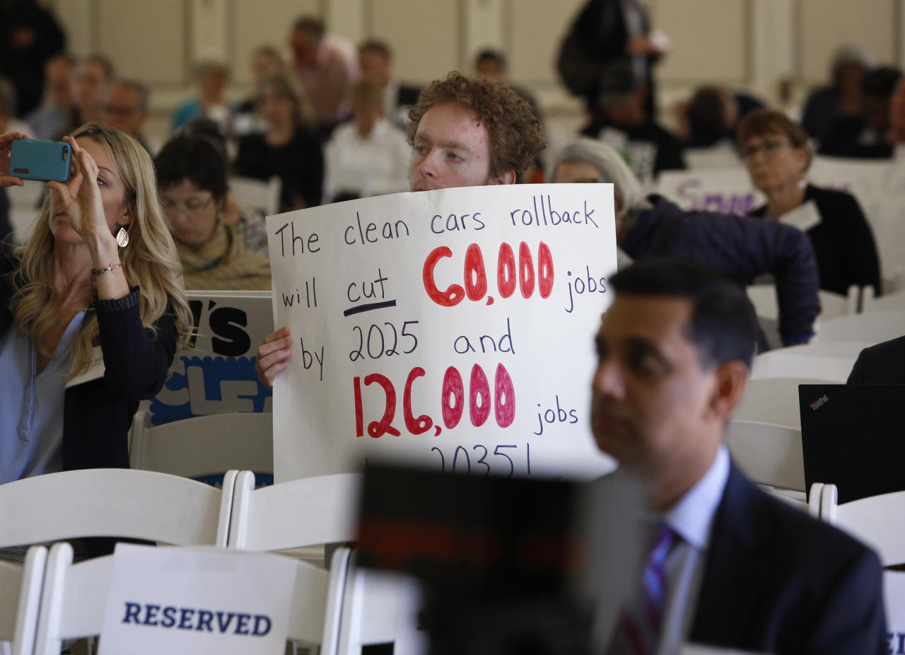 Benjamin Tuggy holds a sign while listening to speakers during the first of three public hearings on the Trump administration's proposal to roll back car-mileage standards in a region with some of the nation's worst air pollution Monday, Sept. 24, 2018 in Fresno, Calif. The day-long session by the U.S. Environmental Protection Agency and National Highway Traffic Safety Administration is a means to gather public comment concerning the mileage plan, which would freeze U.S. mileage standards at levels mandated by the Obama administration for 2020, instead of letting them rise to 36 miles per gallon by 2025. (AP Photo/Gary Kazanjian)