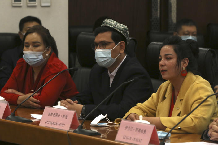 Gulbostan Rozi, right, a representative of ethnic minority women in Kashgar in western China's Xinjiang Uyghur Autonomous Region, speaks as two other Uyghur residents of Xinjiang listen during a press conference at the Ministry of Foreign Affairs in Beijing, Thursday, March 18, 2021. China on Thursday accused Adrian Zenz, a scholar and outspoken critic of its policies toward Muslim minorities, of fabricating charges that have helped bring sanctions against Chinese officials and companies operating in the Xinjiang region. (AP Photo/Sam McNeil)