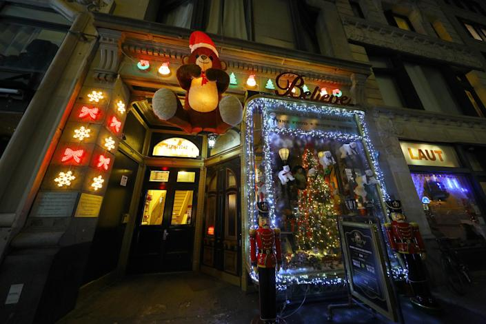 A large teddy bear and Christmas lights cover the exterior of a tavern in New York City. (Photo: Gordon Donovan/Yahoo News)