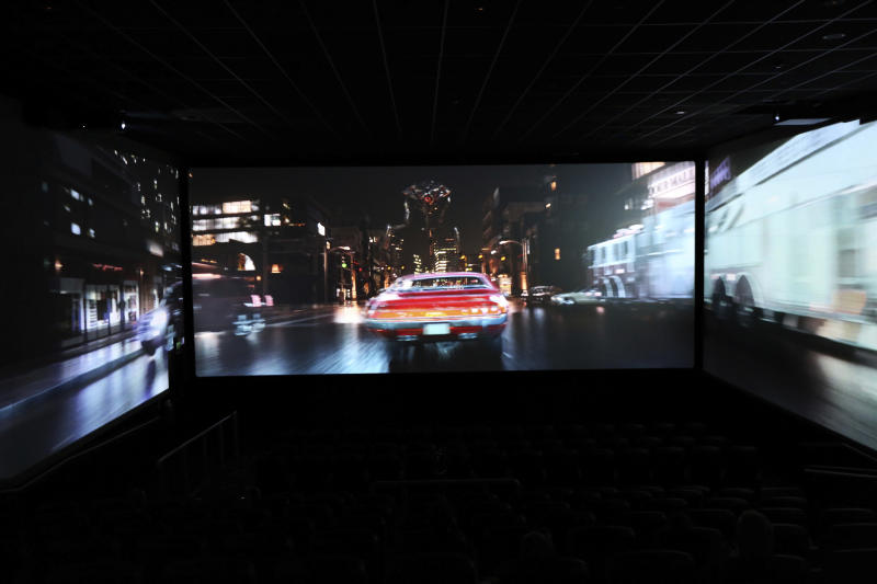 In this photo taken on Thursday, Aug. 9, 2018, a trailer shows a car speeding through traffic as part of a demonstration for ScreenX at Cineworld in London. Sit at the back of the movie theater, and it's possible to see the appeal of ScreenX, the latest attempt to drag film lovers off the sofa and away from Netflix. Instead of one screen, there are three, creating a 270-degree view meant to add to the immersive experience you can't get from the home TV. (AP Photo/Robert Stevens)