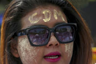 """An anti-coup protester with thanaka, a traditional face paste with letters CDM, representing """"Civil Disobedience Movement"""" shouts slogans during a street march in Mandalay, Myanmar, Thursday, Feb. 25, 2021. Protesters against the military's seizure of power in Myanmar were back on the streets of cities and towns on Thursday as regional diplomatic efforts to resolve Myanmar's political crisis intensified Wednesday. (AP Photo)"""