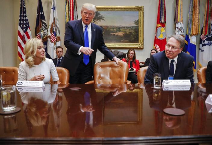 President Donald Trump takes his seat next to National Rifle Associations (NRA) Executive Vice President and Chief Executive Officer Wayne LaPierre, right, and Pastor Paula White, left, of the New Destiny Christian Center, at a 2017 White House meeting.