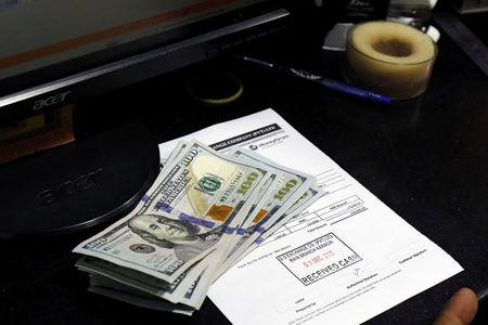 FILE PHOTO: U.S. dollar notes are seen on a desk at a currency exchange booth in Karachi