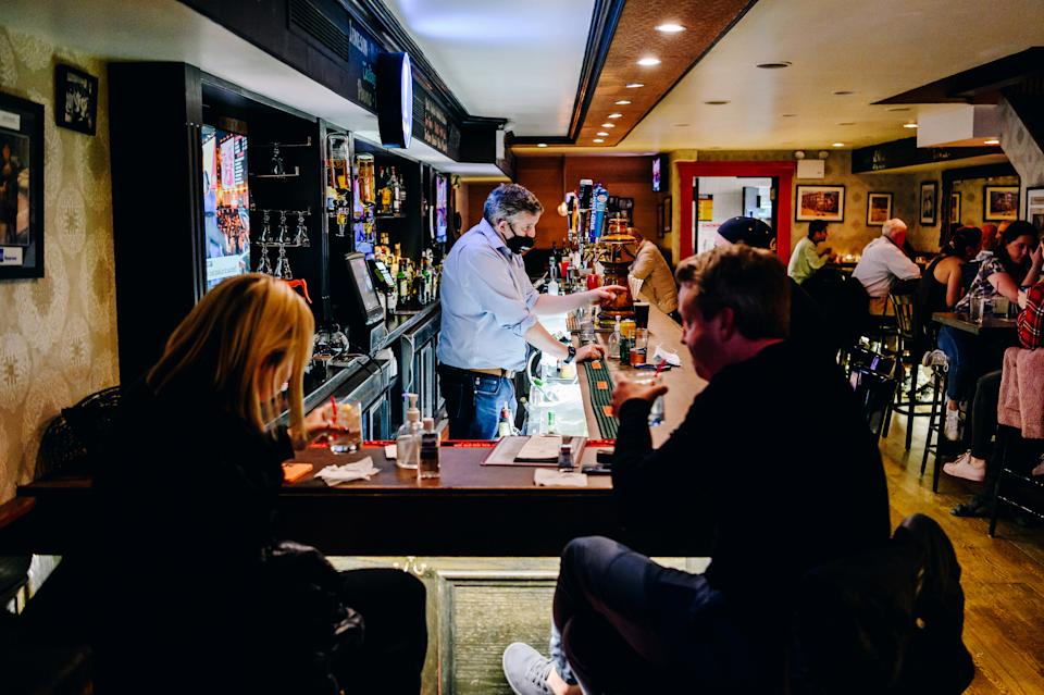 A bartender wearing a protective mask talks to customers sitting at the bar at Blooms Tavern in New York City in May. (Nina Westervelt/Bloomberg via Getty Images)