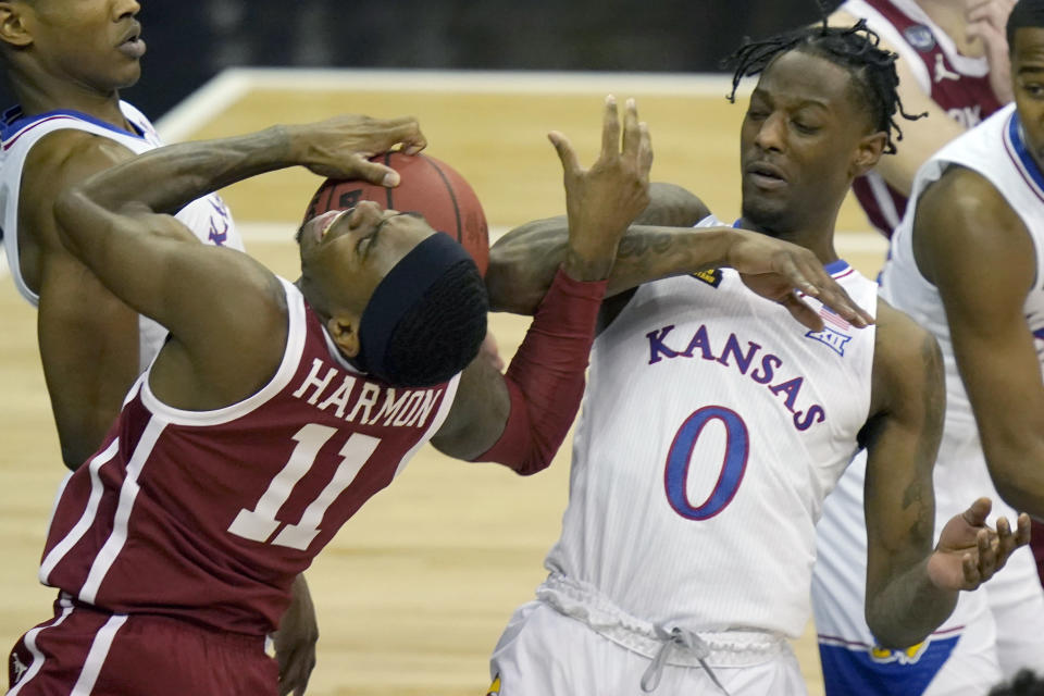 Oklahoma guard De'Vion Harmon (11) is called for traveling while covered by Kansas guard Marcus Garrett (0) during the first half of an NCAA college basketball game in the quarterfinal round of the Big 12 men's tournament in Kansas City, Mo., Thursday, March 11, 2021. (AP Photo/Orlin Wagner)