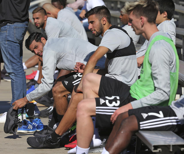 Carlos Vela, left, and Diego Rossi, center, sit on the bench after practice during the introduction of players and coaches at the first training camp of the Los Angeles Football Club soccer team on the campus of UCLA in Los Angeles Monday, Jan. 22, 2018. (AP Photo/Reed Saxon)
