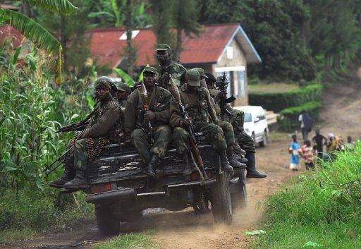 Democratic Republic of Congo government soldiers ride on the back of a truck in Minova, 70 kilometres south of Goma