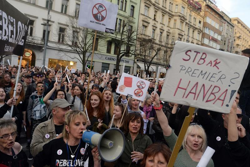 """A protester holds a placard reading """"An STB(state secret security police) agent being Prime minister? Shame!"""" during a rally against the outgoing cabinet led by Czech Prime Minister Andrej Babis on April 9, 2018 in Prague"""