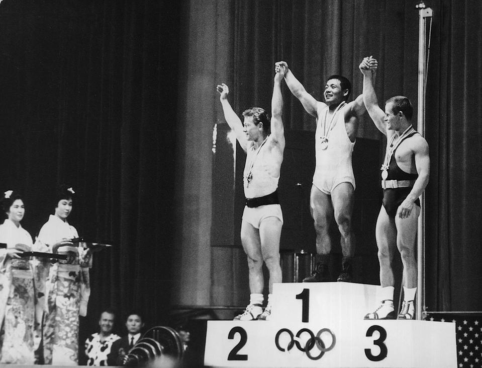 <p>The three winners of the Featherweight Weightlifting event — Isaac Berger of the U.S.A. (silver), Yoshinobu Miyake of Japan (gold) and Mieczyslaw Nowak of Poland (bronze) — raise their hands together on the podium. </p>
