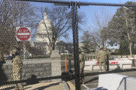 Members of the National Guard stand inside anti-scaling fencing that surrounds the Capitol, Sunday, Jan. 10, 2021, in Washington. Last week's mob attack on the U.S. Capitol starkly highlighted a longstanding local security paradox: The District of Columbia government lacks authority over much of the area within its borders. (AP Photo/Alan Fram)
